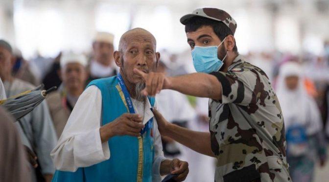 Сотрудник сил безопасности нёс на спине утомлённую ходьбой  пожилую женщину к джамаратам